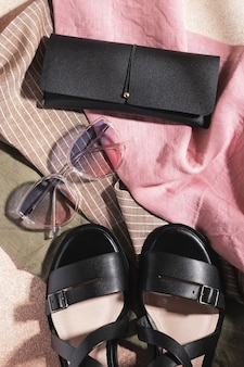 Gradient sunglasses, black leather sandals and black eyeglass case on multicolored fabric