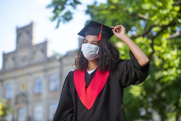 Выпускник. темнокожая милая девушка в академической кепке и в профилактической маске