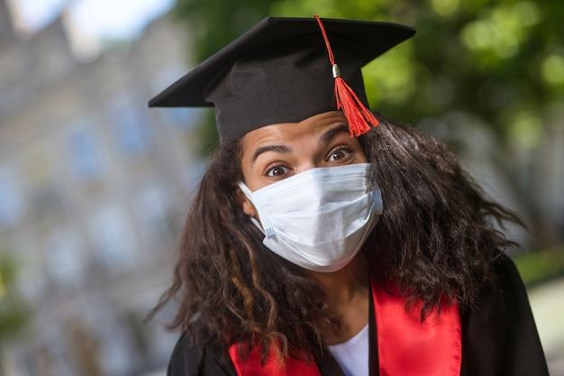 Graduate. a dark-skinned cute girl in academic cap and in a preventive mask