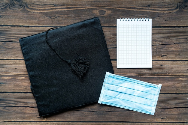 Graduate hat, a notebook and a face mask on wooden background, flat lay