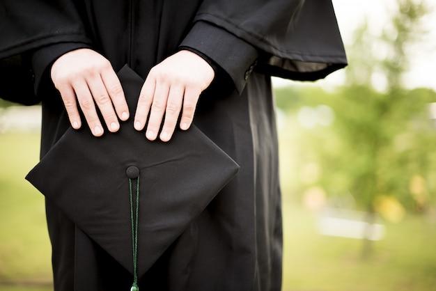 Graduate holding a hat