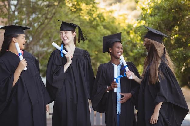 Аспиранты, стоящие со свитком степени в кампусе в школе