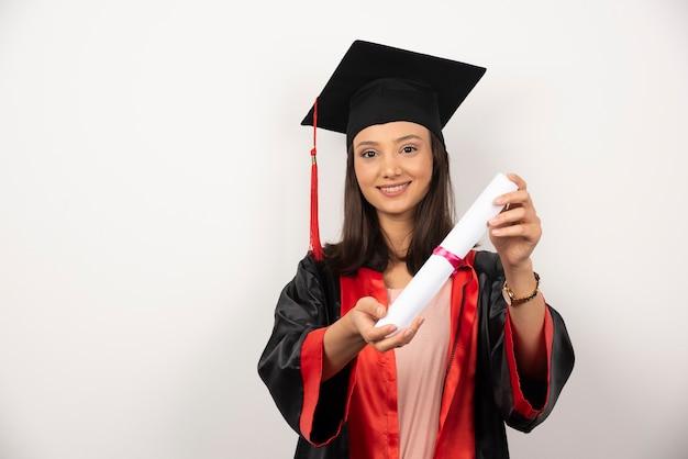 Studente laureato che mostra il suo diploma su sfondo bianco.