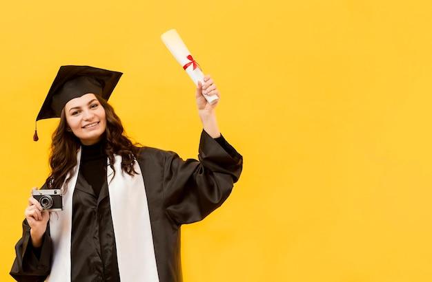 カメラと卒業証書を持つ大学院生