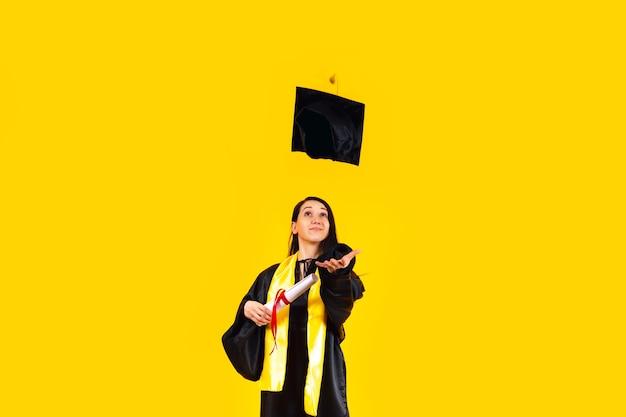 Выпускник с дипломом, подбрасывая свою выпускную фуражку в воздух и празднуя над желтой стеной
