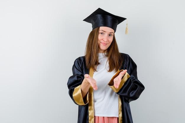 캐주얼 옷, 유니폼 및 쾌활한 찾고 환영 제스처를 하 고 대학원 여자. 전면보기.