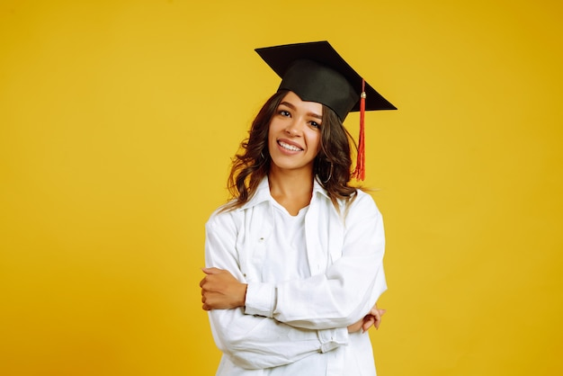 Graduate woman in a graduation hat on her head posing on yellow