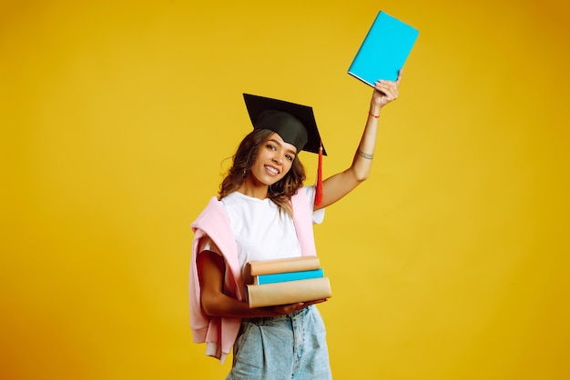 Graduate woman in a graduation hat on her head, with books on yellow.