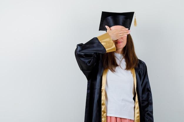 Выпускница женщина держит руку на глазах в повседневной одежде, униформе и выглядит обнадеживающей. передний план.