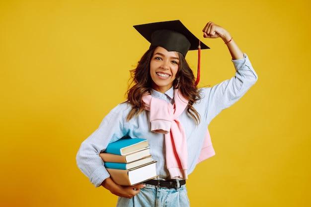 黄色の本で彼女の頭に卒業の帽子の大学院の女性。