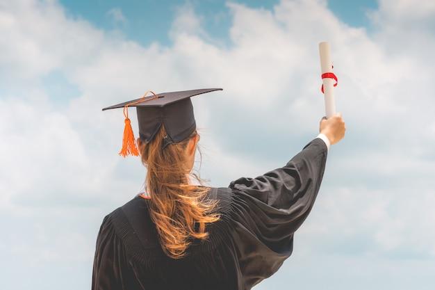 Женщина выпускника в кепке и платье празднует с сертификатом в руке