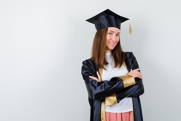 Выпускница женщина в повседневной одежде, униформе, стоя со скрещенными руками и уверенно выглядящей, вид спереди.
