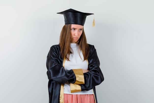 Выпускница женщина в повседневной одежде, стоя в униформе со скрещенными руками и выглядела мрачно, вид спереди.