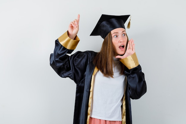 卒業生の女性が上を向いて、カジュアルな服装で開いた口の近くに手を保ち、制服を着て驚いています。正面図。