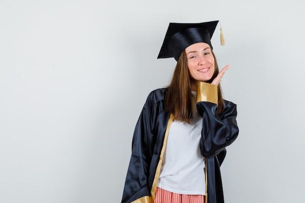 カジュアルな服装で、制服を着て、繊細に見える顔の近くで手でポーズをとる大学院の女性。正面図。