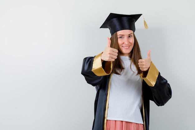 Donna laureata che mostra i doppi pollici in su in abbigliamento casual, uniforme e che sembra allegra. vista frontale.