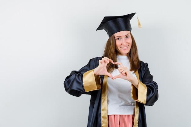 대학원 여자 캐주얼 옷, 유니폼에 심장 제스처를 보여주는 기쁜 찾고. 전면보기.