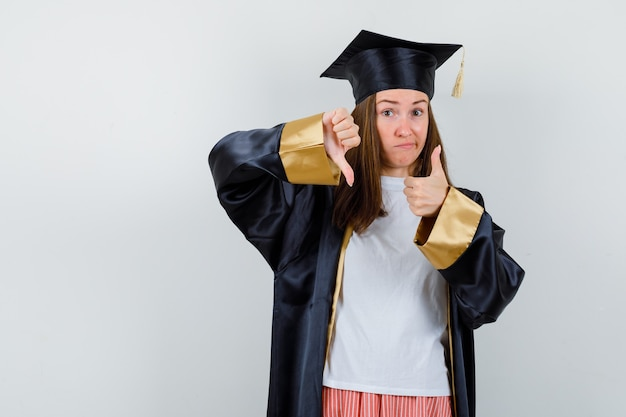 Donna laureata che mostra i pollici su e giù in abiti casual, uniforme e dall'aspetto indeciso. vista frontale.