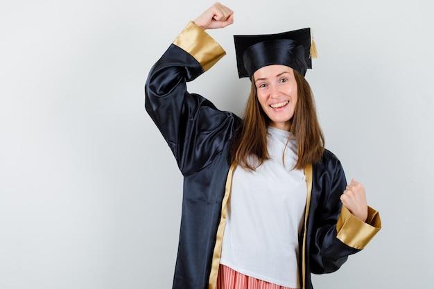 Donna laureata che mostra il gesto del vincitore in abbigliamento casual, uniforme e beata, vista frontale.