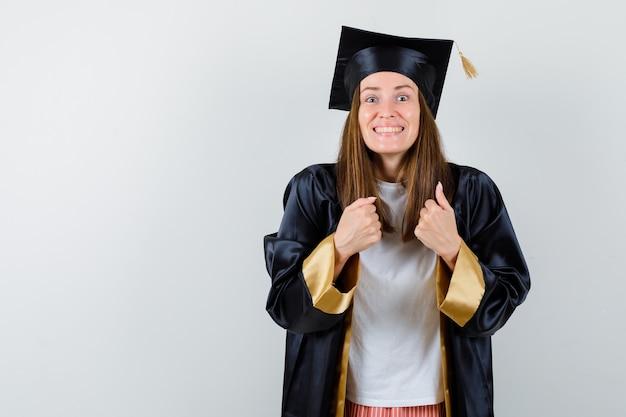 대학원 여자 캐주얼 옷, 유니폼에 승자 제스처를 보여주는 행복을 찾고. 전면보기.