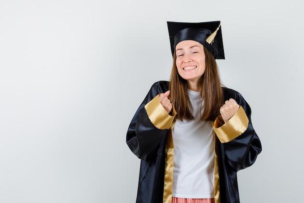 カジュアルな服装で勝者のジェスチャーを示し、制服を着て幸運に見える大学院の女性。正面図。