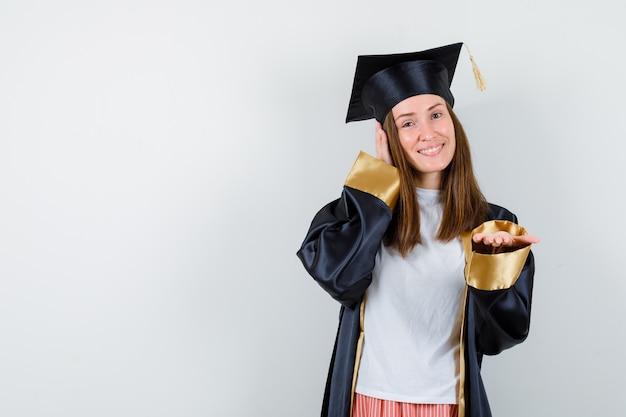 大学院生の女性がカメラに手を広げ、もう一方の手をカジュアルな服装で耳に当て、制服を着て希望に満ちた正面図。
