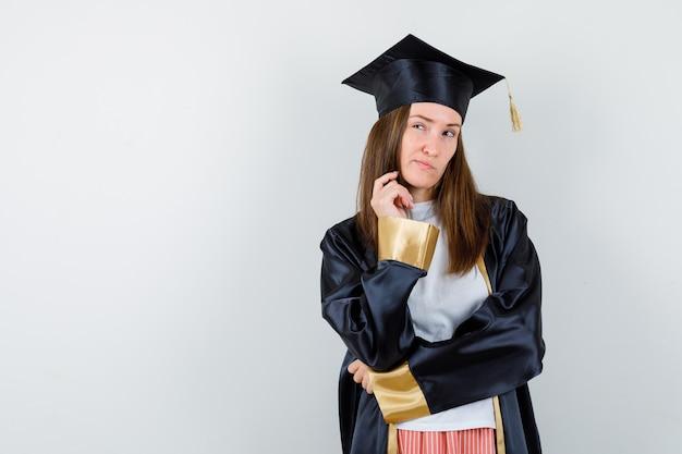 Donna laureata in piedi in posa pensante, labbra curve in abiti casual, uniforme e sguardo esitante, vista frontale.