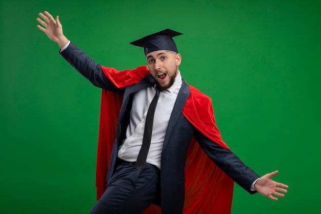 緑の壁の上に立っている赤いマントの幸せで興奮した大きく開いた手で卒業した男