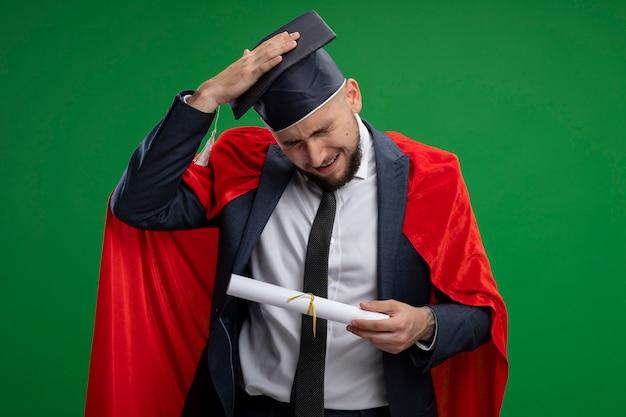 緑の壁の上に立っている間違いのために彼の頭の手で混乱しているように見える卒業証書を保持している赤いマントの卒業生
