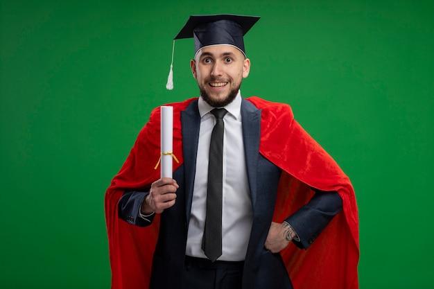 Uomo laureato in mantello rosso che tiene diploma sorridente felice e allegro in piedi sopra la parete verde