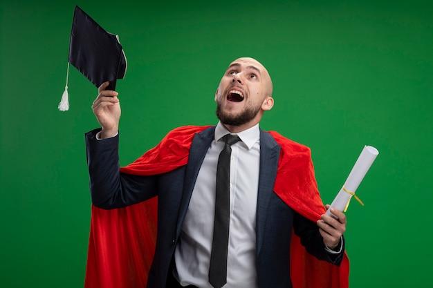 Uomo laureato in mantello rosso che tiene il diploma gettando il suo berretto in piedi felice ed emozionato sopra la parete verde