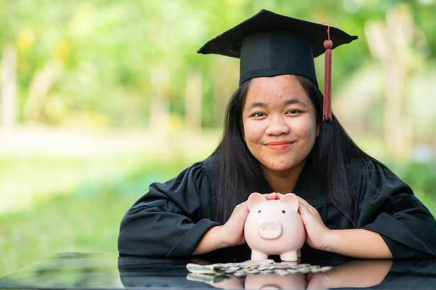 Graduates holding piggy banks saving concept