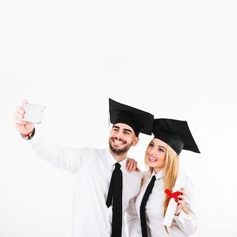 Graduating couple in mortarboards taking selfie