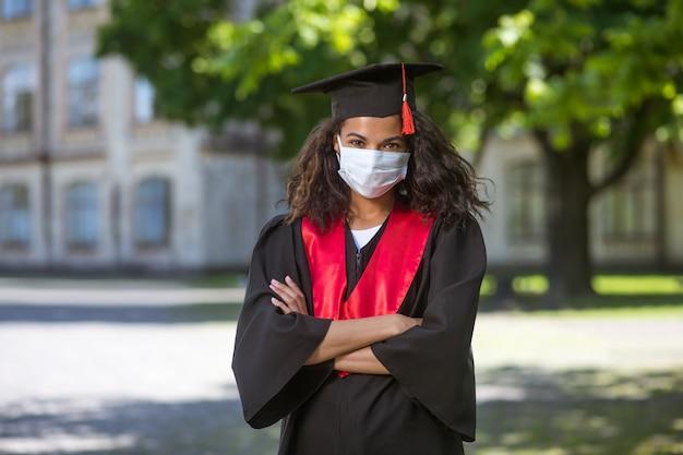 Выпускной темнокожая девушка в академической мантии и в профилактической маске