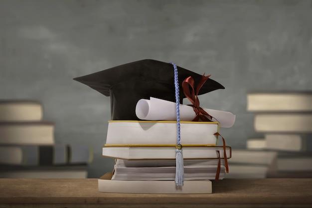 Выпускной колпак над стопкой книг с дипломной бумагой
