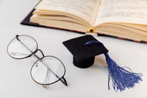 開いた本のクローズアップと卒業帽とメガネ。教育の概念。