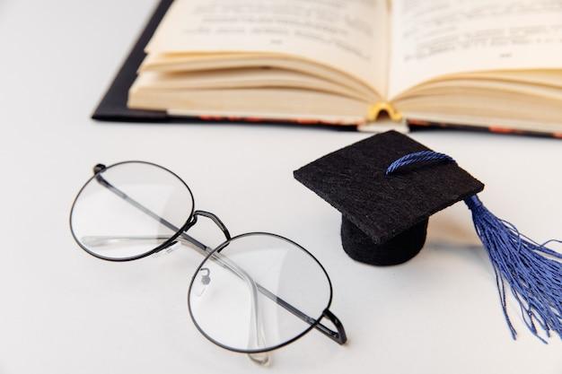 Вручение диплома крышка и очки с крупным планом открытой книги.