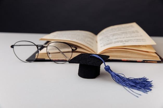 テーブルの上に開いた本と卒業帽とメガネ。教育の概念。