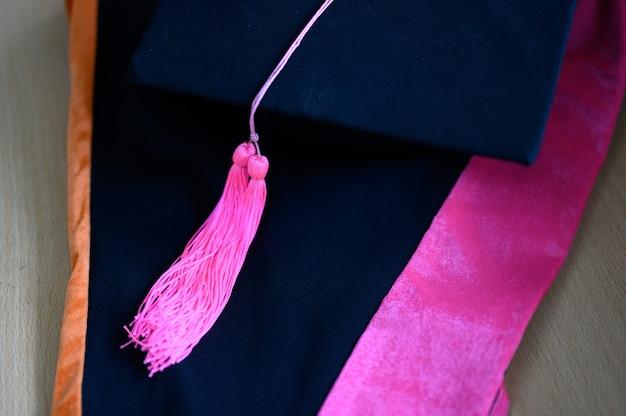Graduation cap, black, yellow tassel, put on a black dress.