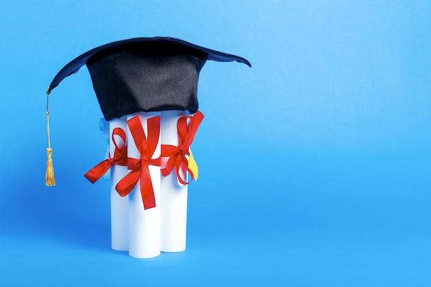 Graduation cap on diplomas on blue background