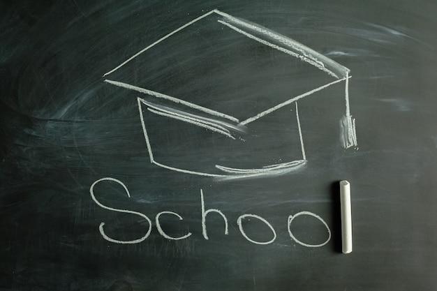 Graduation cap drawn on black chalkboard