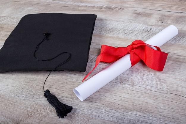 졸업 모자, 나무 테이블 졸업 개념에 학위 종이가 있는 모자.