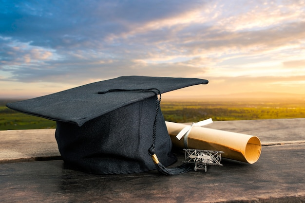 Graduation cap, hat with degree paper on wooden table