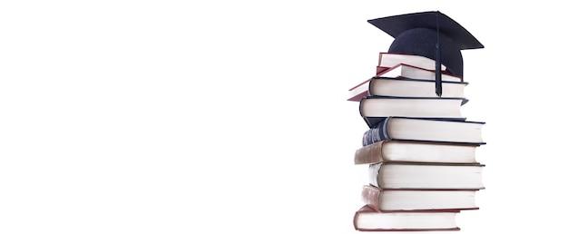 白い背景で隔離の本の高さのスタックの卒業帽