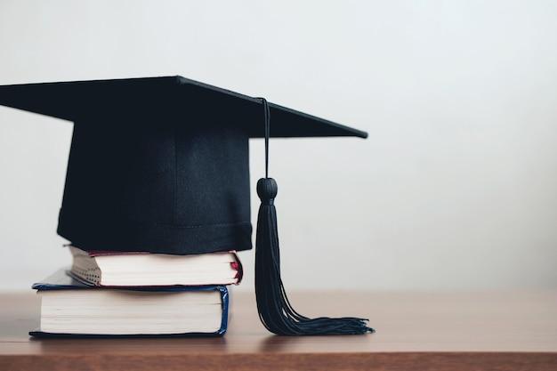 右側に空きスペースがある本のスタックの卒業帽卒業コンセプト