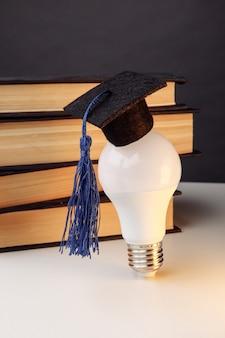 Вручение диплома крышка на лампочке с крупным планом книги. идея образования. вертикальное изображение.