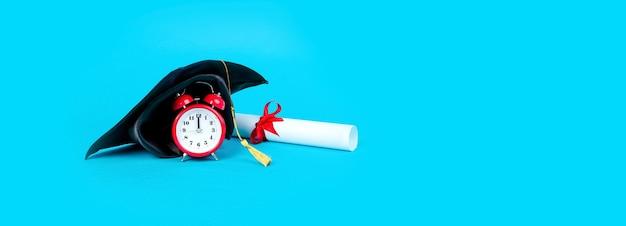 卒業証書の近くの赤い時計の卒業帽