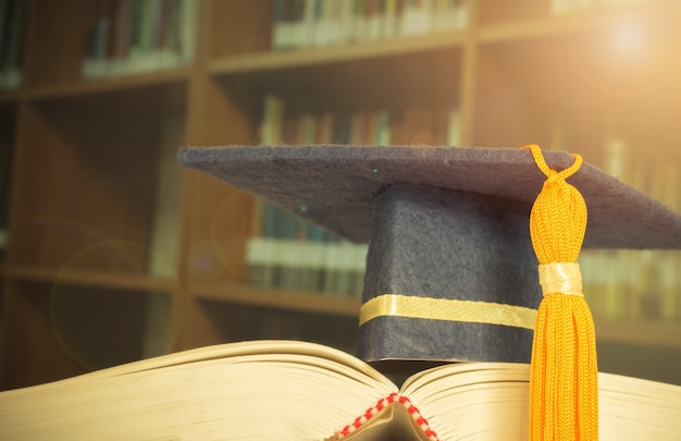 Graduation cap on opening textbook in old library stack of text literature on table