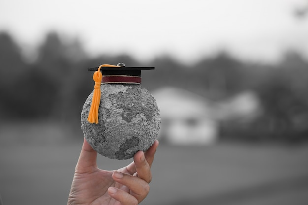 Graduation cap on students holding gray paper mache craft earth globe