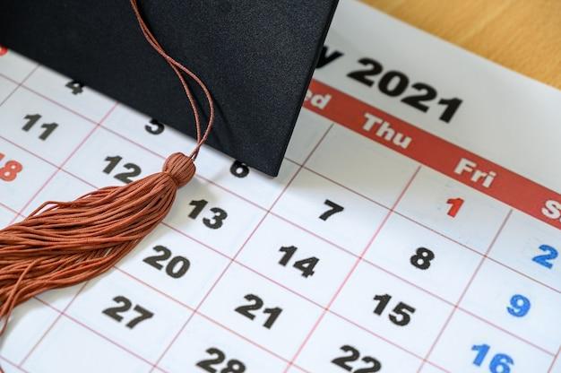 Graduation cap on white calendar
